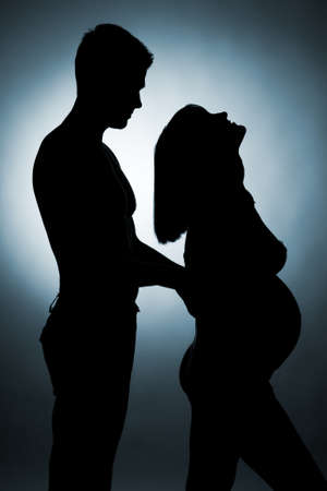 Silhouette of a young couple expecting a baby photo