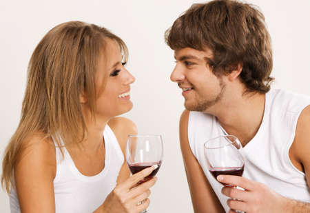 Cheerful young couple drinking wine on green sofa photo