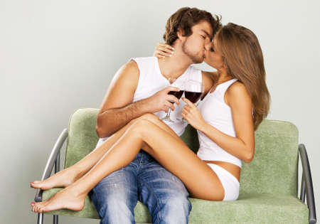 red jeans: Cheerful young couple drinking wine on green sofa