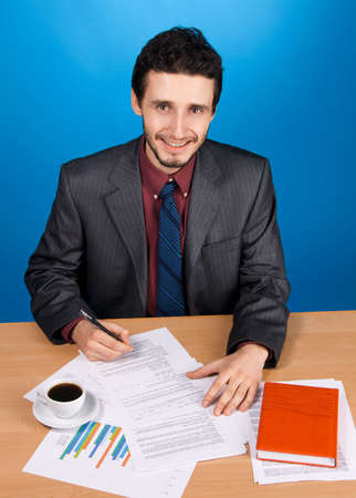 busy beard: Young handsome businessman working with documents, blue background