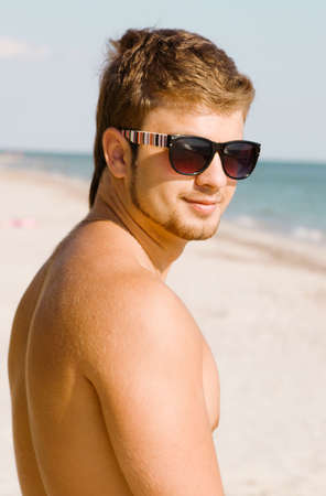 Young man in sunglasses resting on the seaside photo