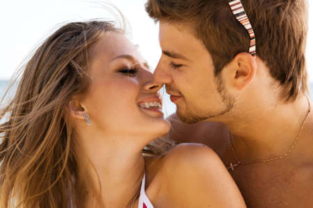 adult dating: Young beautiful couple kissing at the sea shore