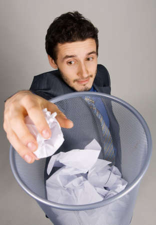 Young businessman playing baskteball with crumpled paper photo
