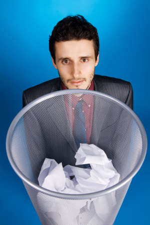 Young businessman playing baskteball with crumpled paper, blue background photo