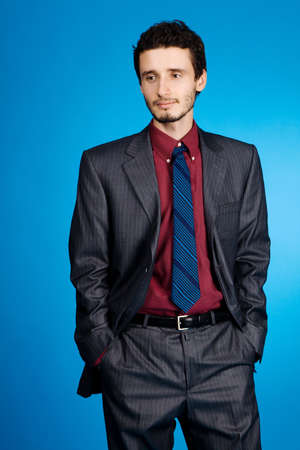 Young handsome businessman studio portrait, blue background Stock Photo - 6352212