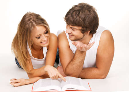 Young cheerful couple reading a book, white background photo