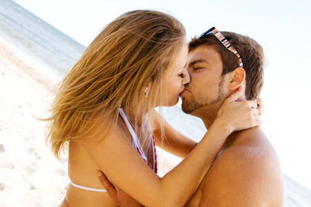 Young beautiful couple kissing at the sea shore photo