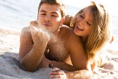Romantic couple having fun on the seaside, focus on the sand grains