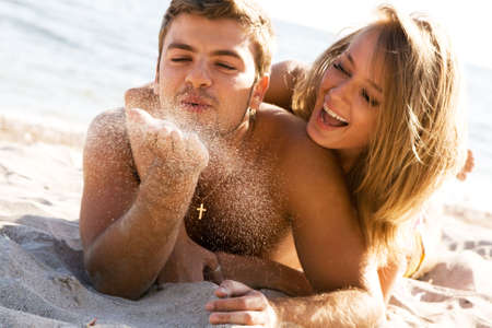 sexy couple on beach: Romantic couple having fun on the seaside, focus on the sand grains