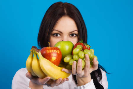 Beautiful young girl with a bunch of fruits, with I love you sign on apple, blue background photo