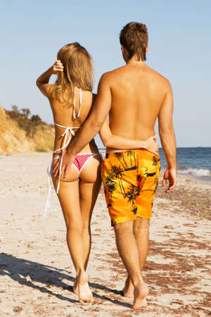Young beautiful couple walking along the beach