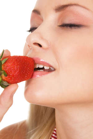 Beautiful girl tasting a strawberry, face portrait photo