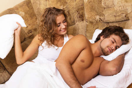 Beautiful young couple waking up, home interior photo