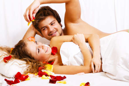 sensual couple: Beautiful couple in rose petals in bedroom