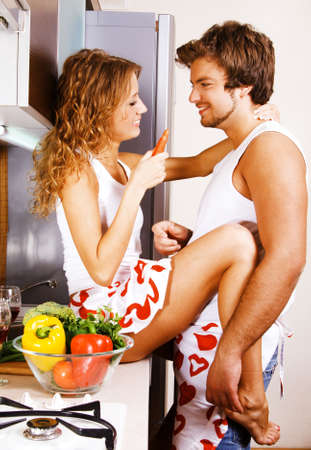 vegetables young couple: Young beautiful couple having fun in the kitchen