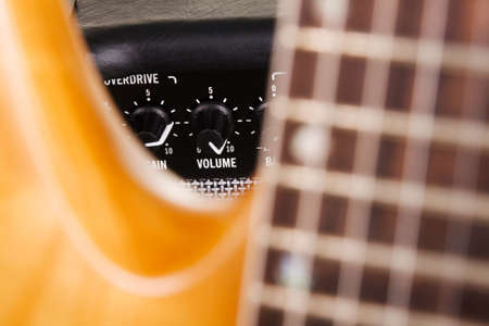 Electric guitar with amplifier, extreme closeup on volume knob photo