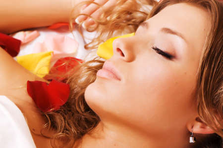 Beautiful young woman lying in rose petals, face closeup photo