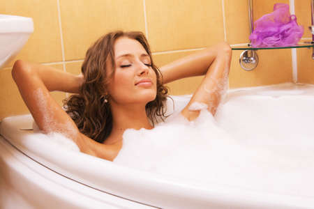 fürdő: Young beautiful woman relaxing in a bath Stock fotó