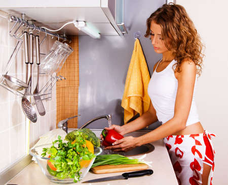Young beautiful woman washing vegetables in the kitchen photo