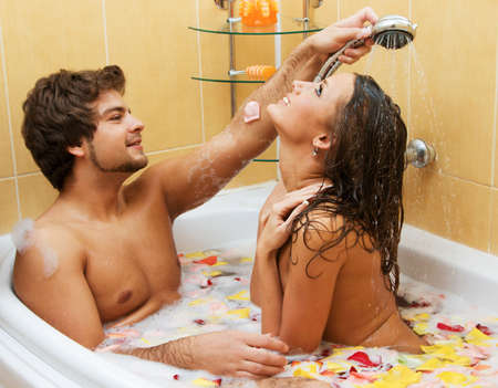 Beautiful young couple enjoying a bath with rose petals Stock Photo - 6787381