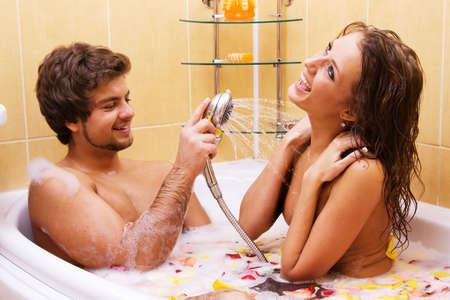 couple bathroom: Beautiful young couple enjoying a bath with rose petals Stock Photo