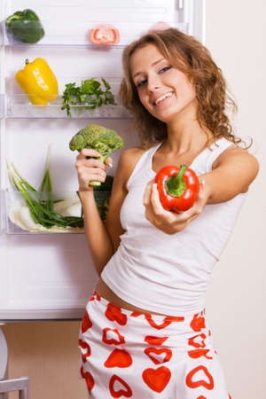 Cheerful young woman taking vegetables out of fridge photo