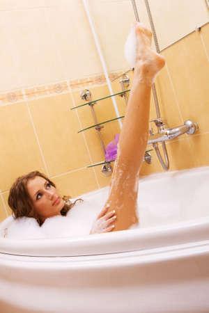 Lady with beautiful long legs taking a bath photo