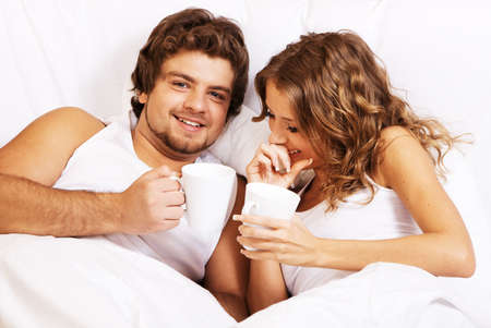 Young beautiful couple enjoying coffee in bed photo