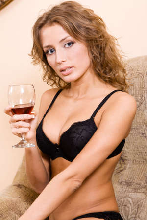 Beautiful woman in black lingerie drinking red wine photo