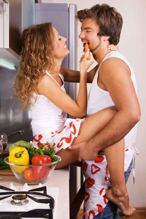 vegetables young couple: Young beautiful couple in their kitchen