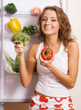 Cheerful young woman taking vegetables out of fridge Stock Photo - 6922373