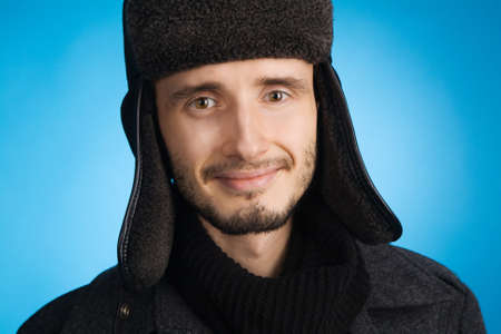 Handsome young man in winter clothing, blue background photo