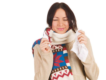 Cute young woman sneezing, with nose spray and handkerchief in her hands photo