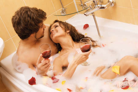 bathroom woman: Beautiful young couple enjoying a bath with rose petals Stock Photo