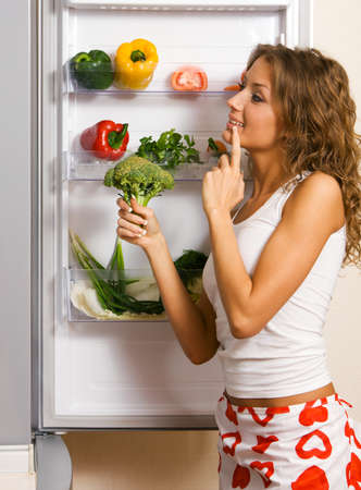 Cheerful young woman taking vegetables out of fridge Stock Photo - 7012822