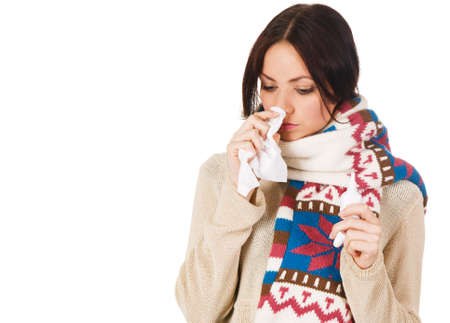 allergic: Cute young woman havign caught cold, with nose spray and handkerchief in her hands Stock Photo