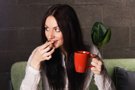 Beautiful lady drinking tea with chocolate candies  photo