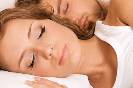 Young beautiful couple sleeping in bed photo