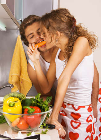 Young beautiful couple having fun in the kitchen photo