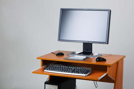 Modern personal computer on a table, on neutral background photo