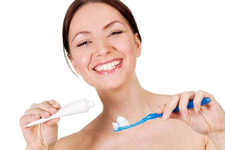 aseo: Hermosa mujer joven sosteniendo la pasta de dientes, cepillo de dientes y fondo blanco Foto de archivo