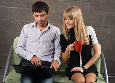 Young man and woman sitting with a laptop indoors photo