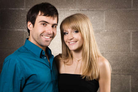Young cheerful couple on brick wall background Stock Photo - 7092321