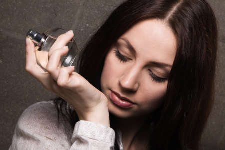 Beautiful lady with a bottle of perfume, face portrait photo