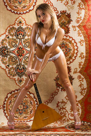 Beautiful woman posing with russian musical instrument balalaika over a traditional west-european carpet photo