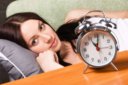 Vintage alarm clock, with beautiful young woman sleeping in the background photo