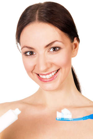 Beautiful young woman holding toothpaste and toothbrush, white background photo