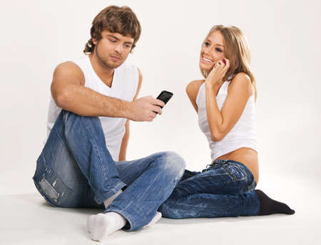 Beautiful couple with mobile phones studio photo Stock Photo - 7154520