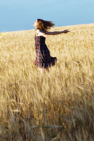 Beautfiul woman in checkered dress in a wheat field photo