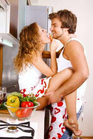 kitchen apron: Young beautiful couple having fun in the kitchen